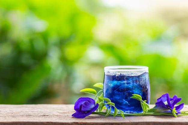 Fleur de pois violet ou de pois bleu frais et jus en verre sur fond de table en bois