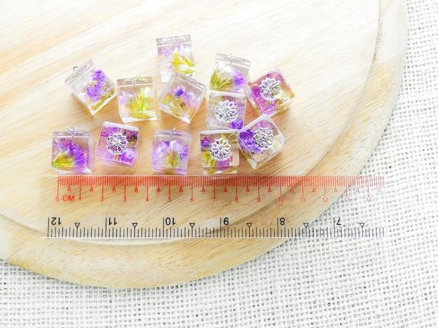 Fleur pourpre séchée dans un pendentif en résine cristalline.