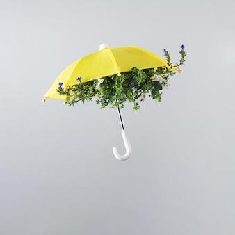 Fleur de printemps arrangée à l'intérieur d'un parapluie jaune isolé sur fond gris clair. motif printanier. disposition carrée avec espace de copie.