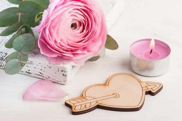Fleur de renoncule rose avec coeur en bois