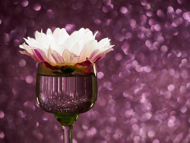 Fleur rose dans un verre sur un fond rose scintillant avec bokeh, copyspace