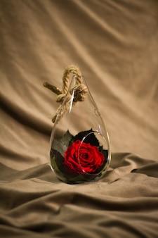 Fleur de rose décorée dans un bol en verre avec cordon