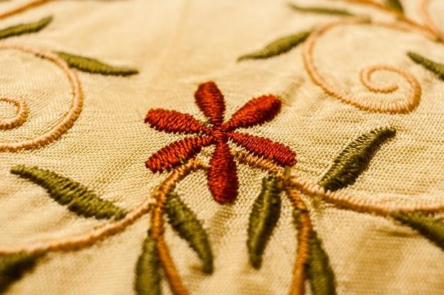 Fleur rouge, feuilles vertes et tiges à boucles, brodées au point satin.