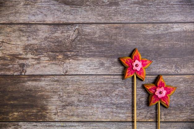 Fleur rouge en pain d'épice peinte à la main sur fond en bois. vue de dessus