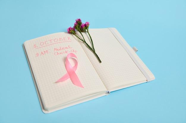 Fleur et ruban rose, symbole de la journée de sensibilisation au cancer du sein, allongé sur une page avec une ligne de bloc-notes avec des inscriptions rappelant un examen médical. 1er octobre, journée internationale du cancer du sein