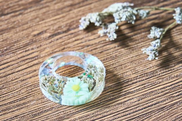 Fleur séchée verte avec boucle d'oreille en résine faite à la main de paillettes colorées sur fond de bois