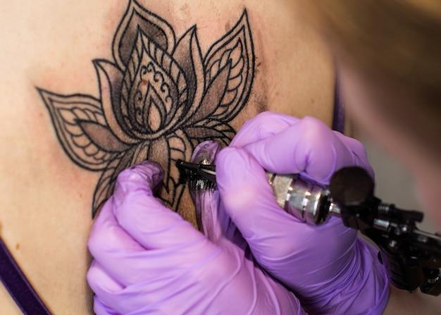 Fleur de tatouage sur le dos de la femme