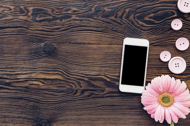 Fleur et téléphone mobile avec écran blanc sur bois, vue de dessus. maquette