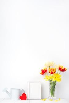 Fleur de tulipe dans un vase en verre avec cadre photo sur mur blanc, concept de décoration de fête des mères.