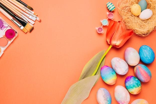 Fleur de tulipe; pinceaux; oeufs de pâques colorés et nid sur fond orange