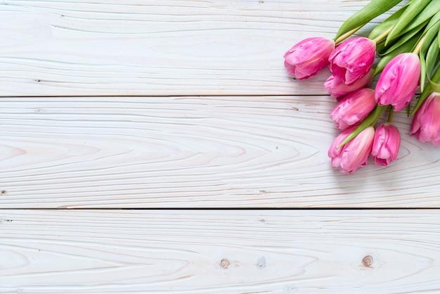Fleur de tulipe rose sur fond de bois