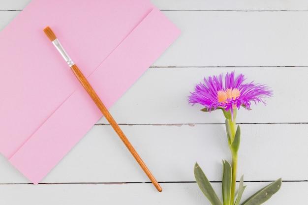 Fleur vue de dessus et pinceau sur fond en bois