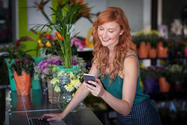 Fleuriste à l'aide de téléphone portable tout en utilisant un ordinateur portable
