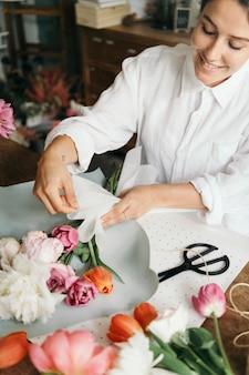 Fleuriste arrangeant un bouquet de fleur