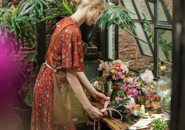 Fleuriste attachant un ruban sur un bouquet