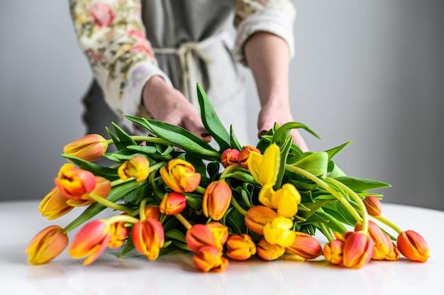 Fleuriste au travail faisant un bouquet de fleurs de tulipes au printemps