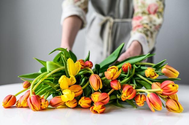 Fleuriste au travail. femme faisant un bouquet de fleurs de tulipes au printemps. fond blanc