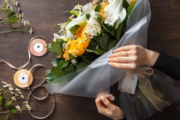 Fleuriste au travail : femme faisant le bouquet moderne de mode de différentes fleurs sur le fond en bois