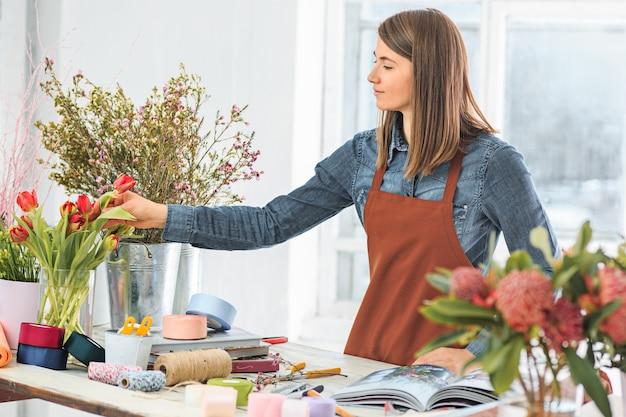 Fleuriste au travail: la jeune fille faisant de la mode un bouquet moderne de fleurs différentes