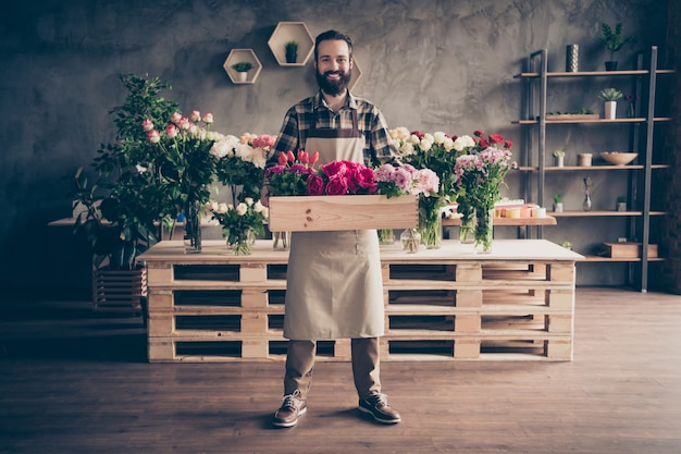 Fleuriste barbu posant dans son magasin de fleurs avec boîte de fleurs