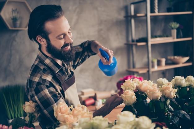 Fleuriste barbu travaillant dans son magasin de fleurs