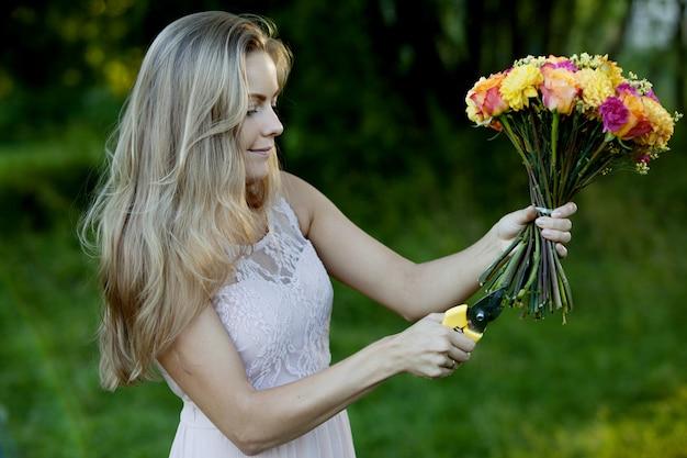 Fleuriste de belle jeune femme. la fille dans le parc dessine un bouquet. de plein air