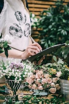 Le fleuriste compte et enregistre les fleurs