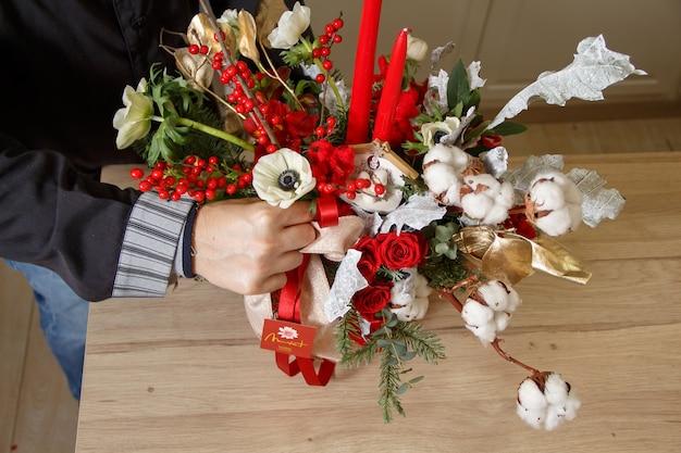 Fleuriste créant une décoration pour la maison de noël ou du nouvel an avec des rubans, des baies, des fleurs et des branches. détail de la célébration des vacances d'hiver, gros plan des mains