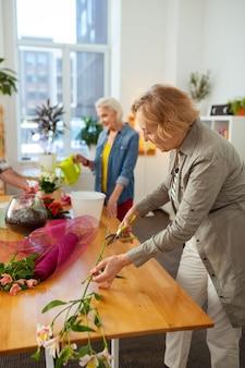 Fleuriste créative. belle femme âgée coupant une branche de fleurs tout en profitant de la fleuristerie