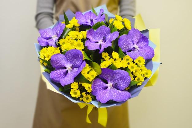 Fleuriste dans un magasin de fleurs. fille détient un beau bouquet de fleurs.