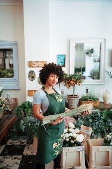 Fleuriste debout dans une boutique tenant un bouquet d'épillets