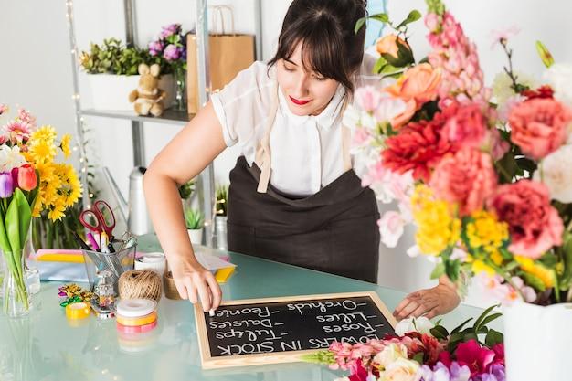 Fleuriste écrivant sur ardoise avec craie