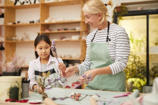 Fleuriste enseignant une fille asiatique