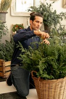 Fleuriste expérimenté taillant les plantes