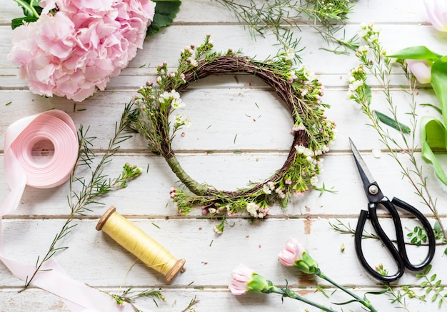Fleuriste faisant l'arrangement de la couronne de fleurs fraîches
