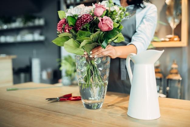 Fleuriste faisant des arrangements de fleurs en boutique