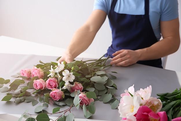 Fleuriste faisant un bouquet à table contre une surface claire