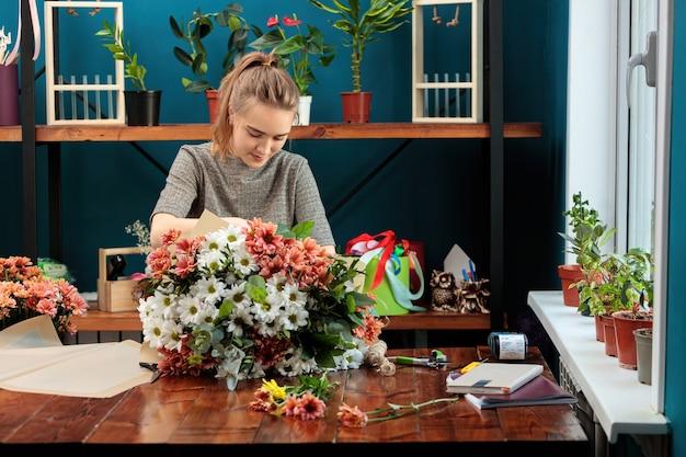 Le fleuriste fait un bouquet de chrysanthèmes multicolores. une jeune fille adulte travaille avec enthousiasme.