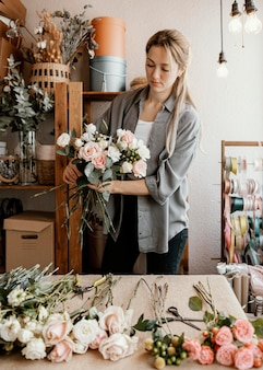 Fleuriste femelle faisant un bel arrangement floral