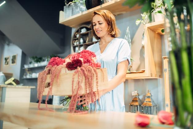 Fleuriste femelle met des fleurs dans un vase, boutique de fleurs