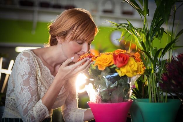 Fleuriste femelle sentant les fleurs roses