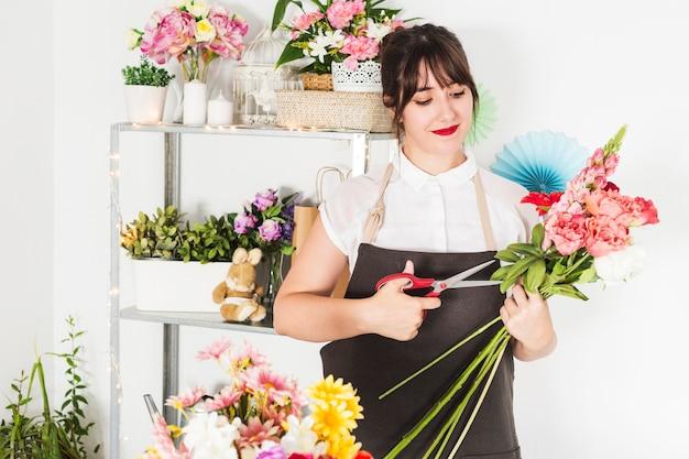 Fleuriste femme coupe des tiges de fleurs avec des ciseaux