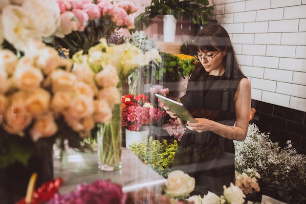 Fleuriste femme dans son propre magasin de fleurs en prenant soin de fleurs