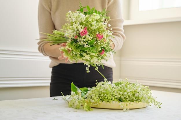 Fleuriste femme avec différentes fleurs sur la table faisant le bouquet