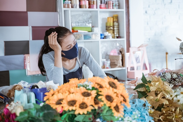 Fleuriste femme ennuyeuse portant tablier et masque facial lean on table seau fleur client en attente au matin