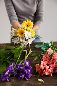 Fleuriste femme faire un bouquet de fleurs colorées