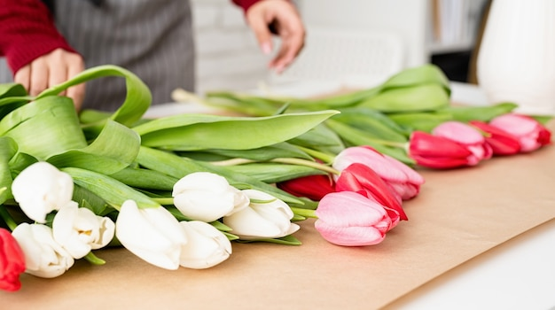 Fleuriste femme faisant un bouquet de tulipes colorées fraîches