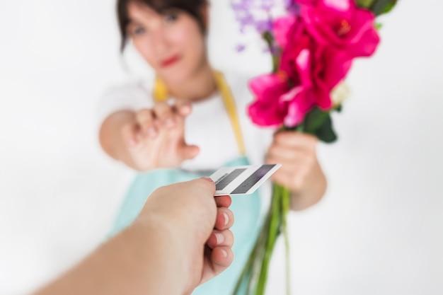 Fleuriste femme avec des fleurs prenant une carte de crédit de son client