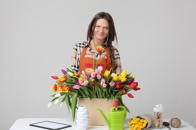 Fleuriste femme sur un mur gris avec des tulipes