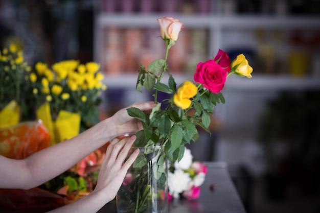 Fleuriste femme organisant un bouquet de fleurs dans un vase